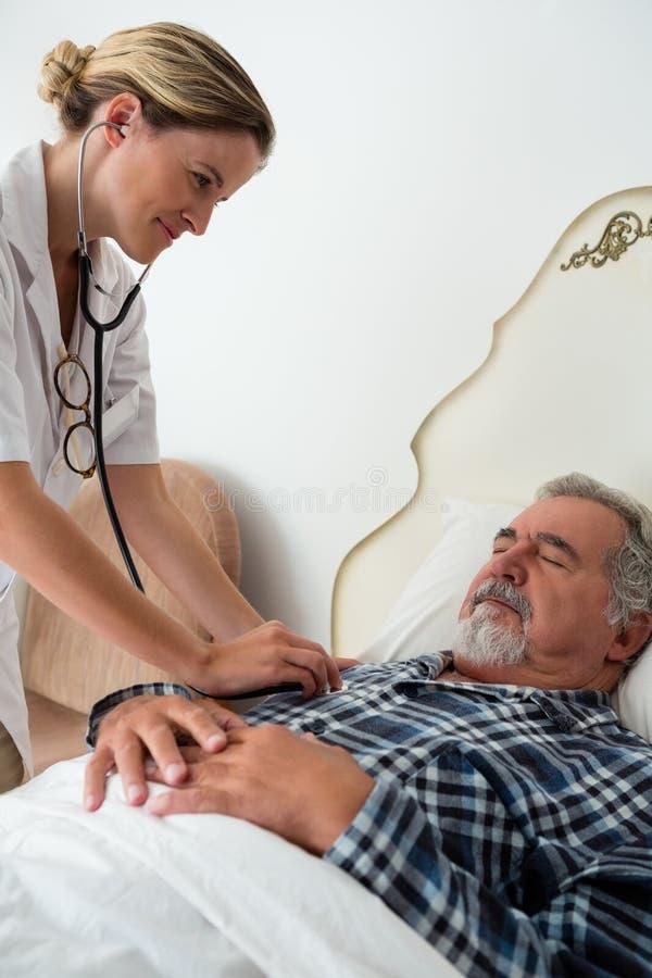 Medico femminile che ascolta i battiti cardiaci dell'uomo senior che dormono sul letto immagini stock libere da diritti