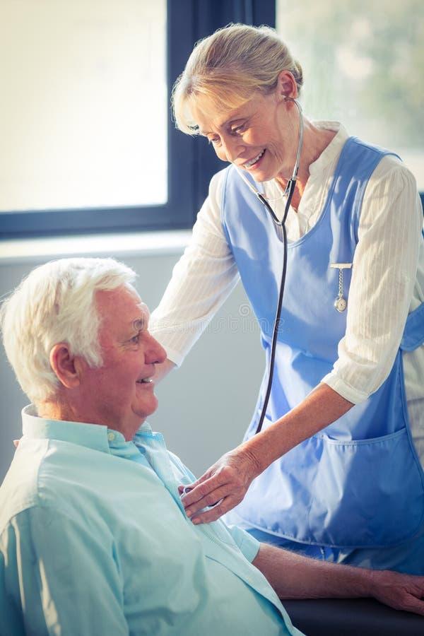 Medico femminile che controlla battito cardiaco dell'uomo senior fotografia stock libera da diritti