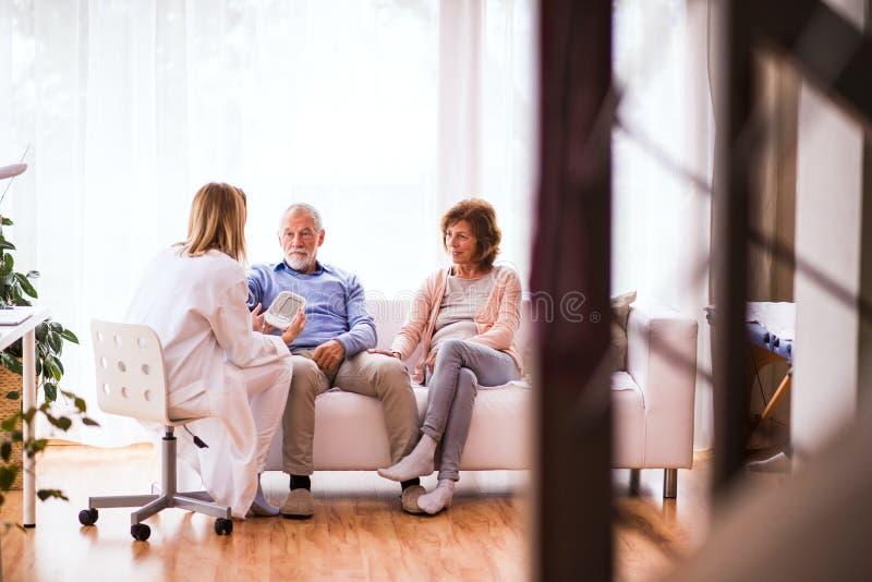 Medico femminile che controlla pressione sanguigna dell'uomo senior fotografia stock libera da diritti