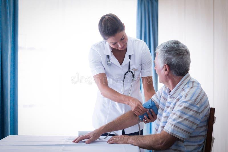 Medico femminile che controlla pressione sanguigna dell'uomo senior immagine stock