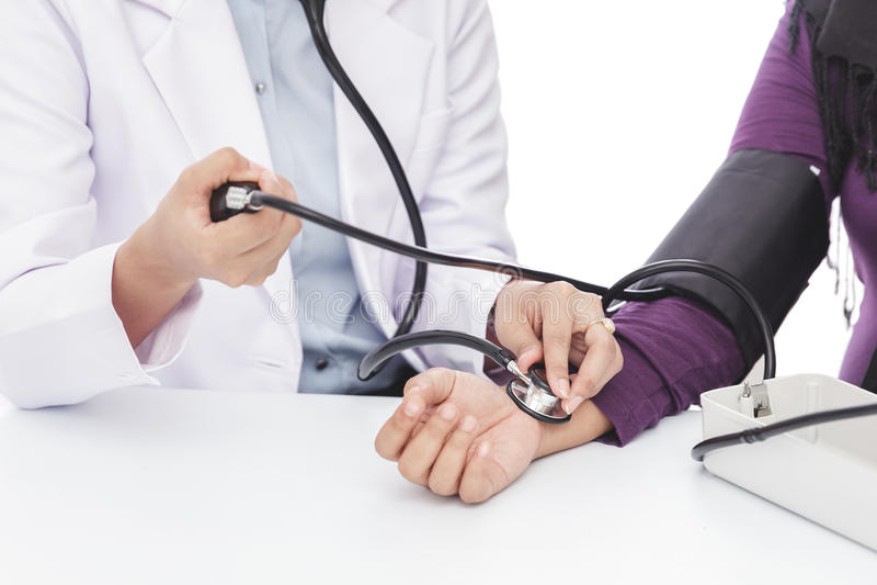 Medico femminile che controlla pressione sanguigna di un paziente fotografia stock