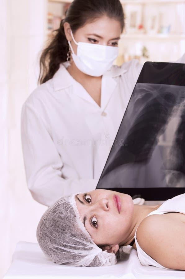 Medico femminile che controlla raggi x di una ragazza immagini stock