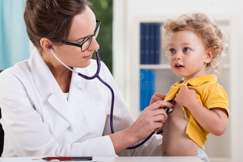 Medico femminile che esamina piccolo ragazzo dolce fotografia stock libera da diritti