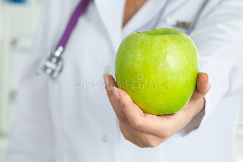 Medico femminile che offre mela verde fotografie stock libere da diritti