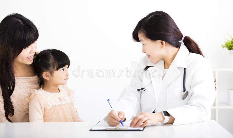 Medico femminile che parla con bambino e madre fotografia stock libera da diritti