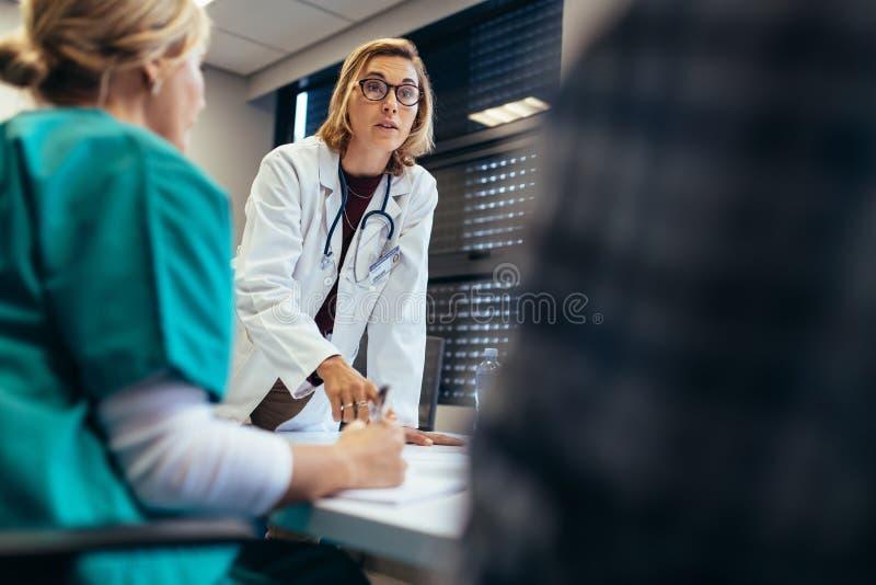 Medico femminile che riassume il suo gruppo nel corso della riunione immagini stock libere da diritti