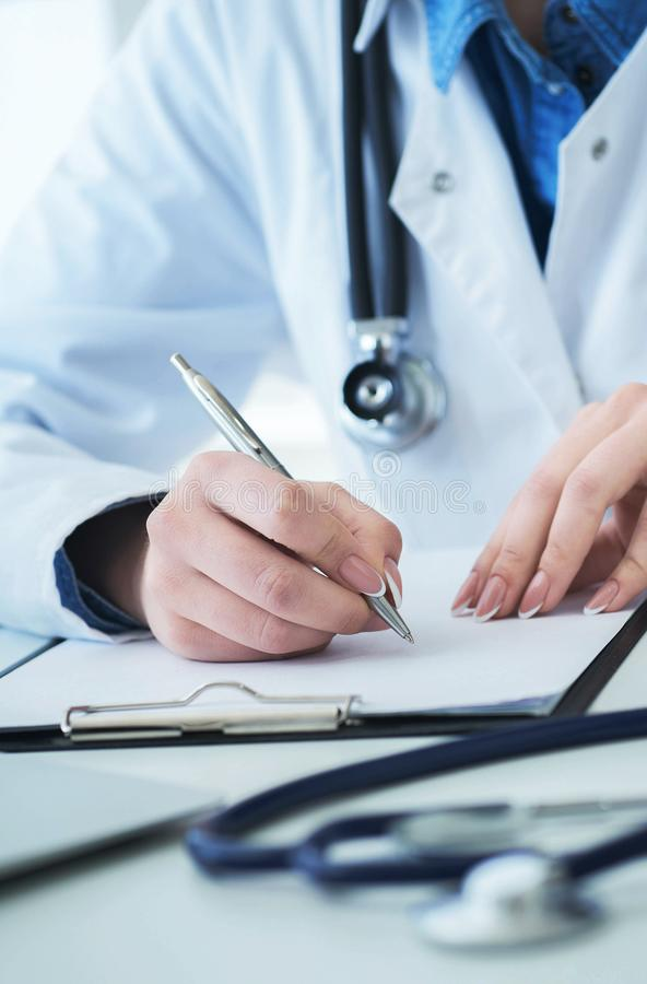 Medico femminile che riempie la forma di prescrizione o la lista di storia del paziente al cuscinetto della lavagna per appunti d fotografia stock
