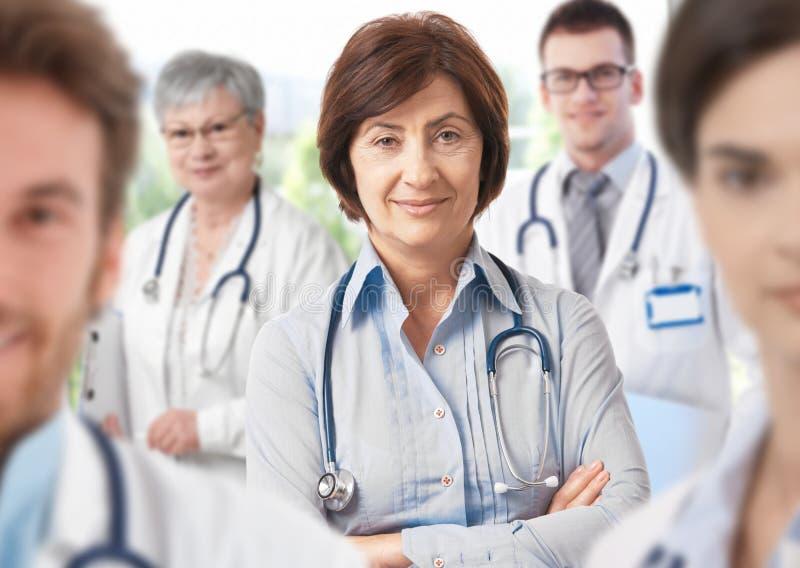 Medico femminile con il gruppo di medici immagini stock libere da diritti