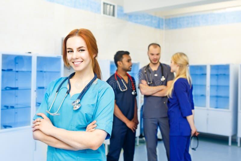 Medico femminile davanti al gruppo, esaminante macchina fotografica e sorridente con il gruppo di medici nel fondo Gruppo multira immagine stock libera da diritti