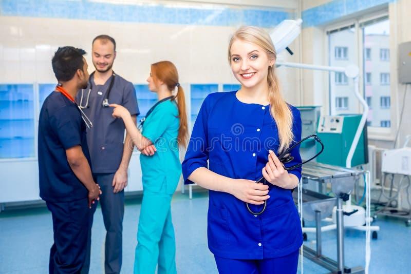 Medico femminile davanti al gruppo, esaminante macchina fotografica e sorridente con il gruppo di medici nel fondo Gruppo multira immagine stock