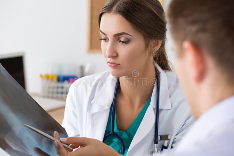 Medico femminile della medicina che mostra qualcosa al suo collega maschio o fotografia stock libera da diritti