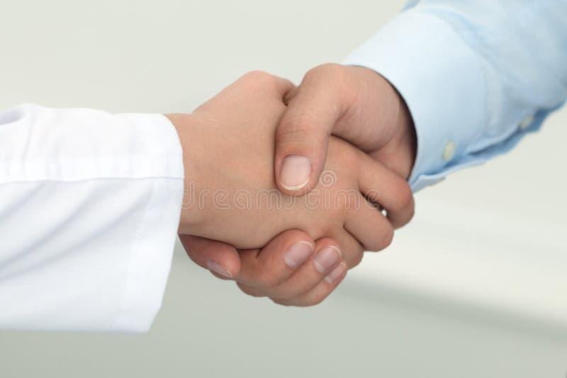 Medico femminile della medicina che stringe le mani con il paziente maschio fotografia stock