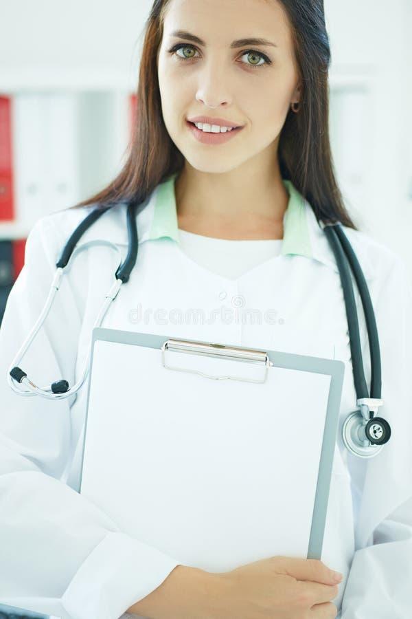 Medico femminile della medicina che tiene una lavagna per appunti con un foglio bianco del primo piano di carta Concetto medico d immagini stock