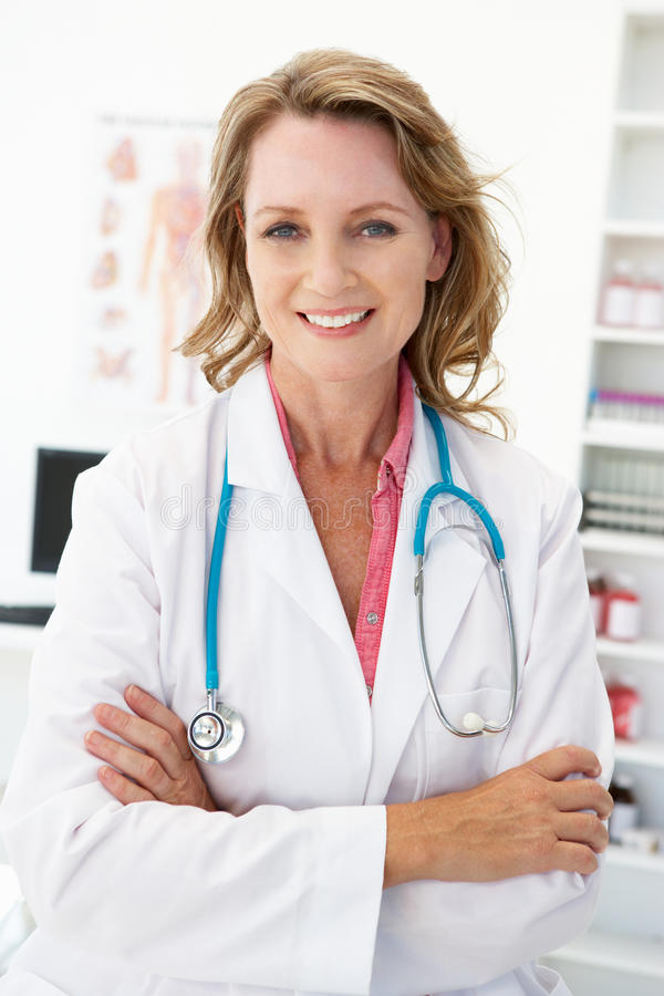 Medico femminile di metà di età felice nella stanza di consulto fotografie stock