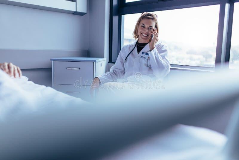 Medico femminile felice che si siede nella stanza di ospedale e che fa un telefono immagini stock libere da diritti