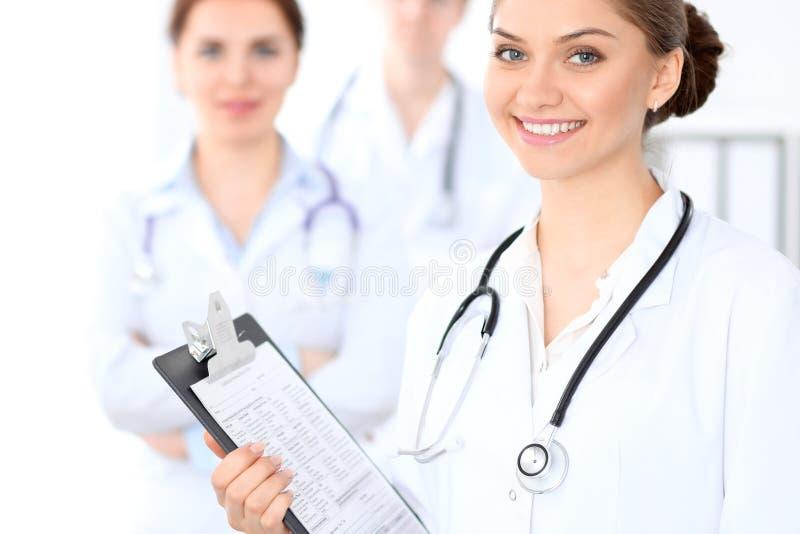 Medico femminile felice che tiene lavagna per appunti medica mentre il personale medico è ai precedenti immagini stock