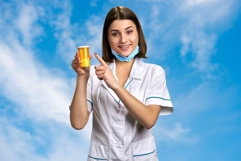 Medico femminile grazioso che indica sulle pillole immagine stock libera da diritti
