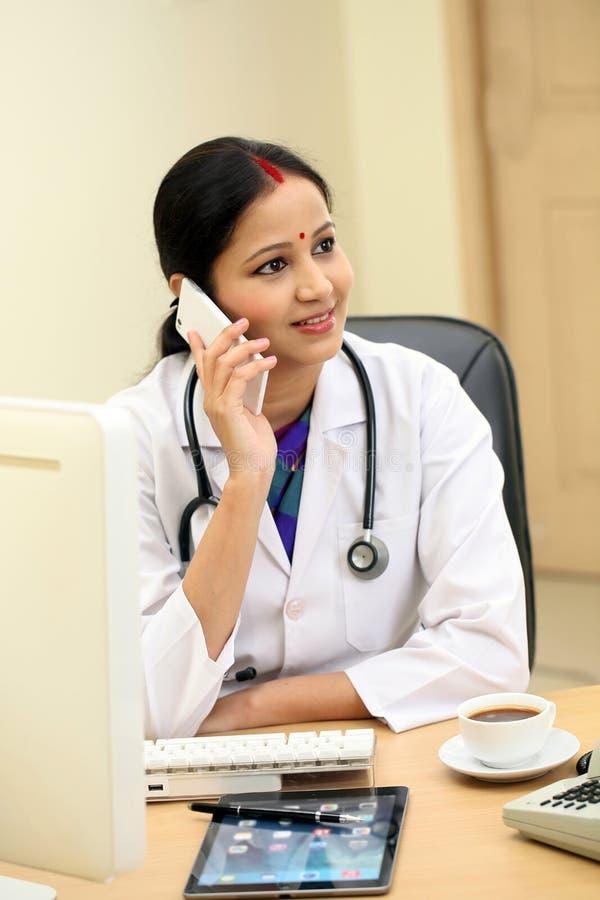 Medico femminile indiano tradizionale che parla sul telefono cellulare fotografie stock