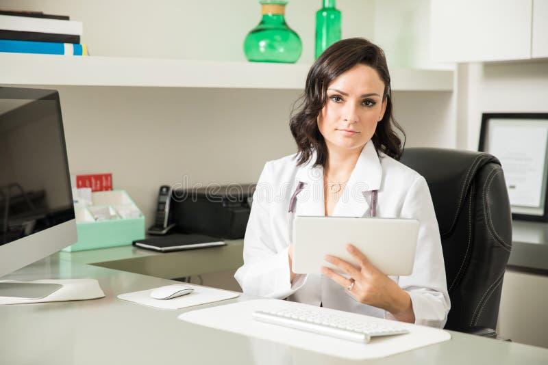 Medico femminile ispano che per mezzo di una compressa immagini stock