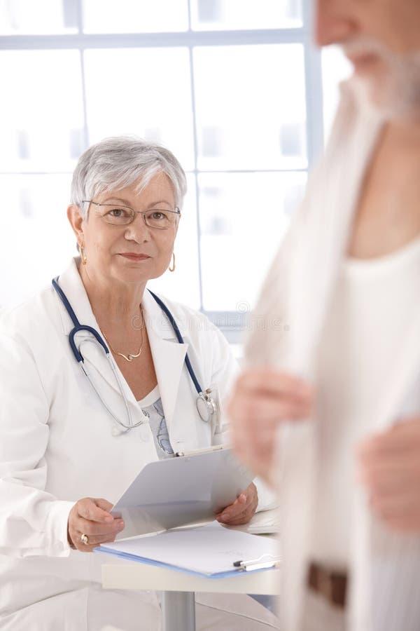 Medico femminile maggiore che esamina paziente immagini stock libere da diritti