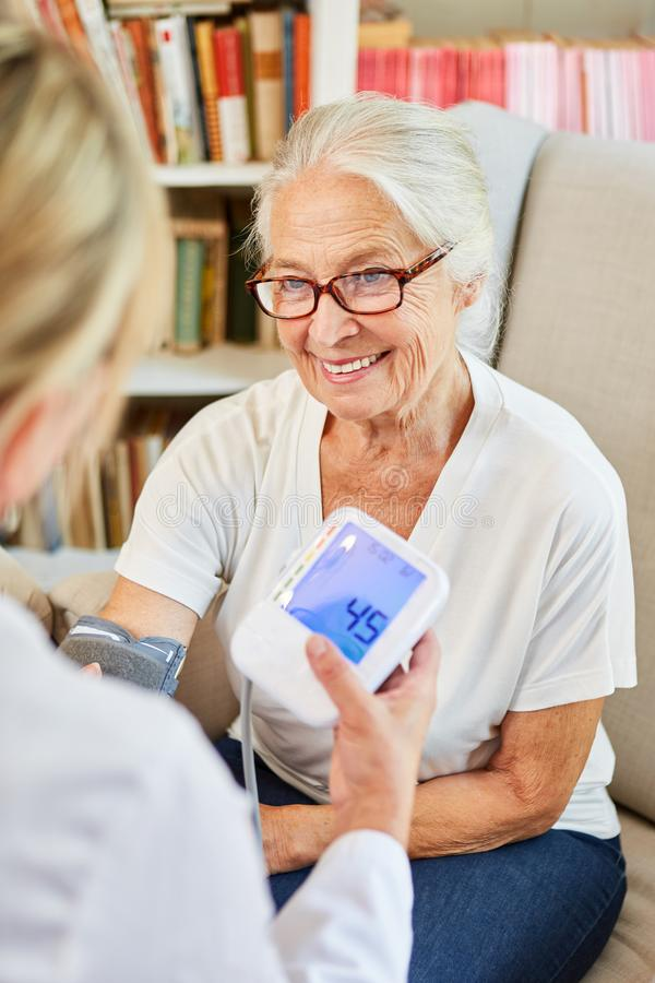 Medico femminile misura la pressione sanguigna con una donna anziana sorridente fotografia stock libera da diritti