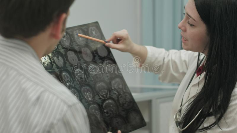 Medico femminile nei raggi x di manifestazione della clinica al paziente maschio immagine stock libera da diritti