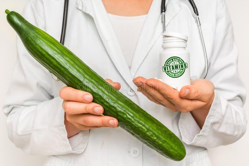 Medico femminile paragona il mucchio delle pillole al cetriolo fresco immagine stock