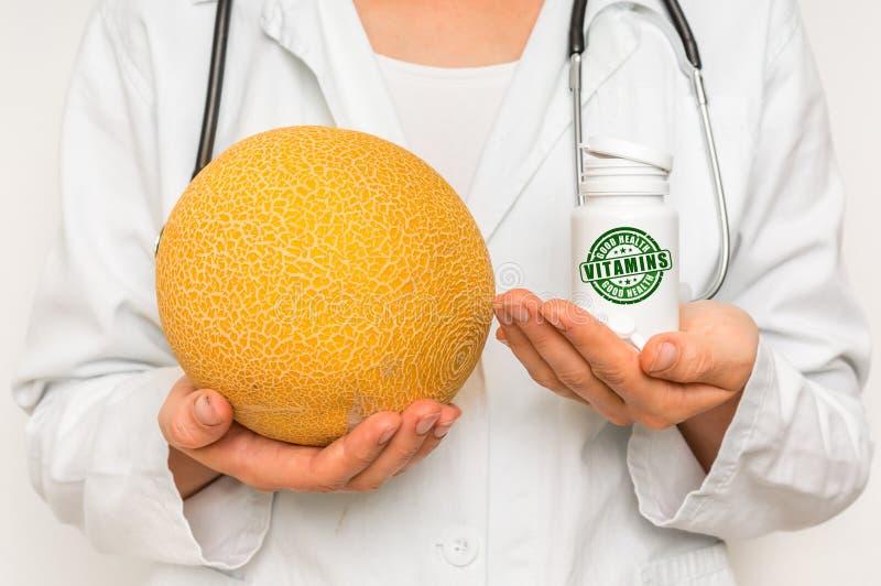 Medico femminile paragona il mucchio delle pillole al melone giallo fresco fotografia stock