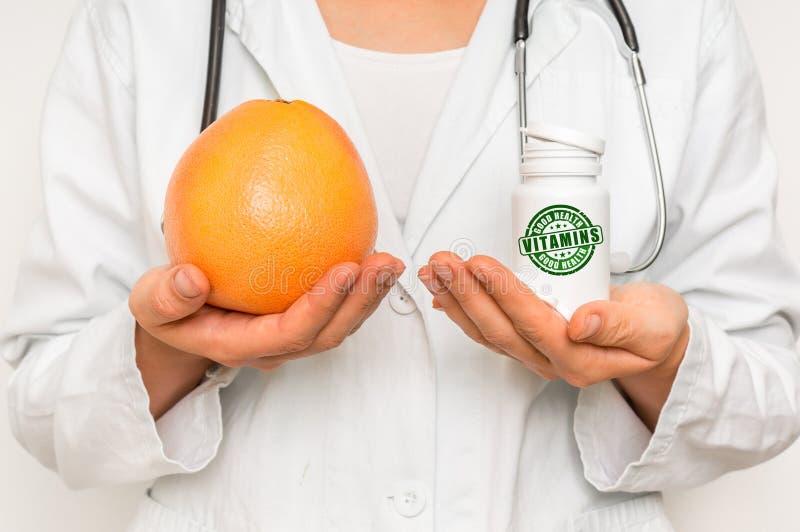 Medico femminile paragona il mucchio delle pillole al pompelmo fresco fotografia stock libera da diritti