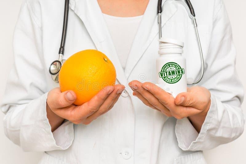 Medico femminile paragona il mucchio delle pillole all'arancia fresca fotografia stock libera da diritti