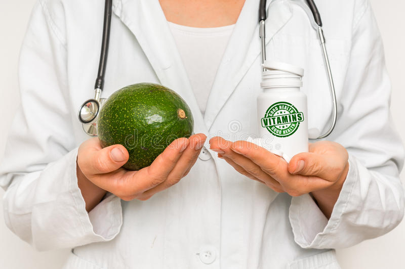 Medico femminile paragona il mucchio delle pillole all'avocado fresco fotografie stock libere da diritti