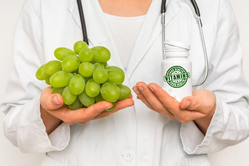 Medico femminile paragona il mucchio delle pillole all'uva fresca fotografie stock
