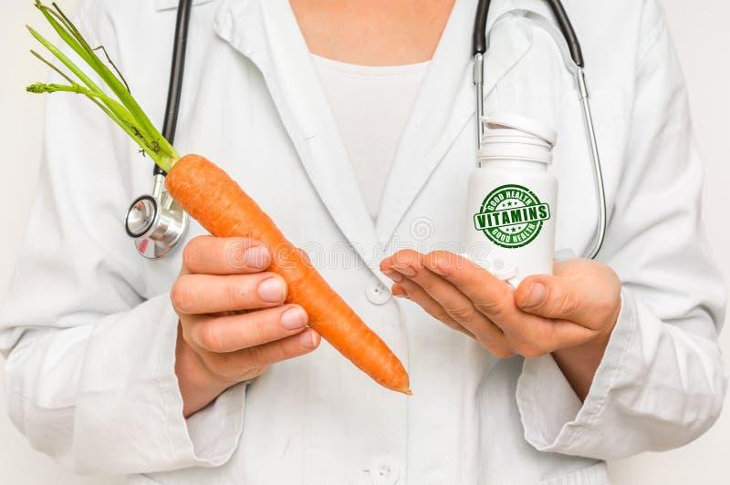 Medico femminile paragona il mucchio delle pillole alla carota fresca fotografia stock libera da diritti