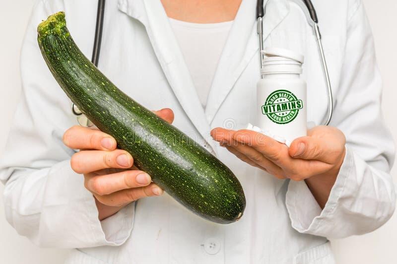 Medico femminile paragona il mucchio delle pillole allo zucchini fresco fotografia stock libera da diritti