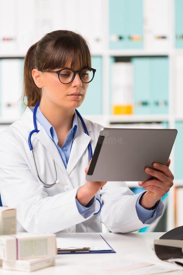 Medico femminile premuroso allo scrittorio facendo uso della compressa immagine stock