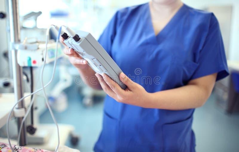 Medico femminile regola l'apparecchio medico elettronico fotografia stock libera da diritti