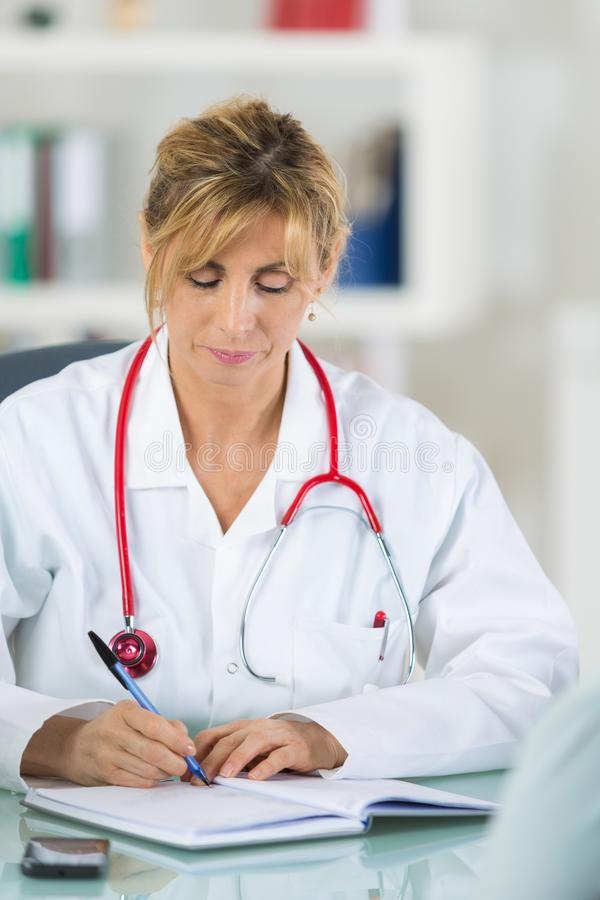 Medico femminile a scrittura dell'ufficio qualcosa nell'ordine del giorno immagine stock libera da diritti