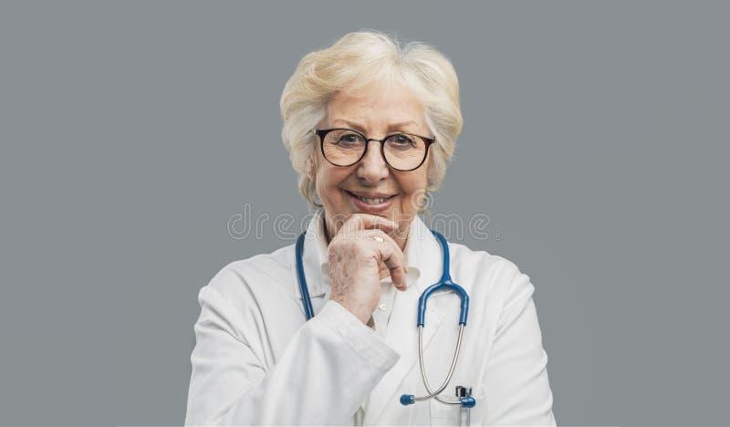 Medico femminile senior che posa e che sorride fotografie stock libere da diritti