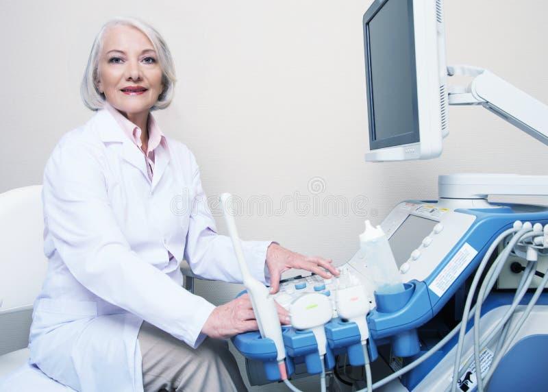 Medico femminile senior che sorride mentre installando la macchina di ultrasuono fotografia stock