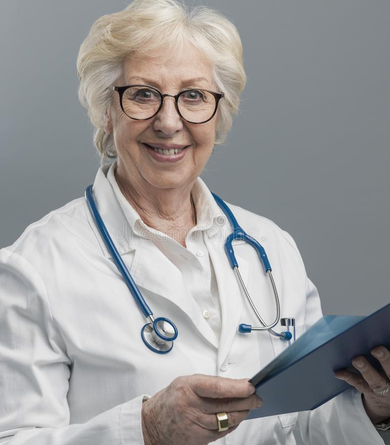 Medico femminile senior sicuro che posa e che sorride immagine stock libera da diritti