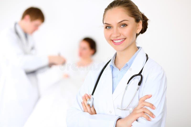 Medico femminile sorridente allegro sui precedenti con il medico ed il suo paziente nel letto Ad alto livello e qualità di immagine stock