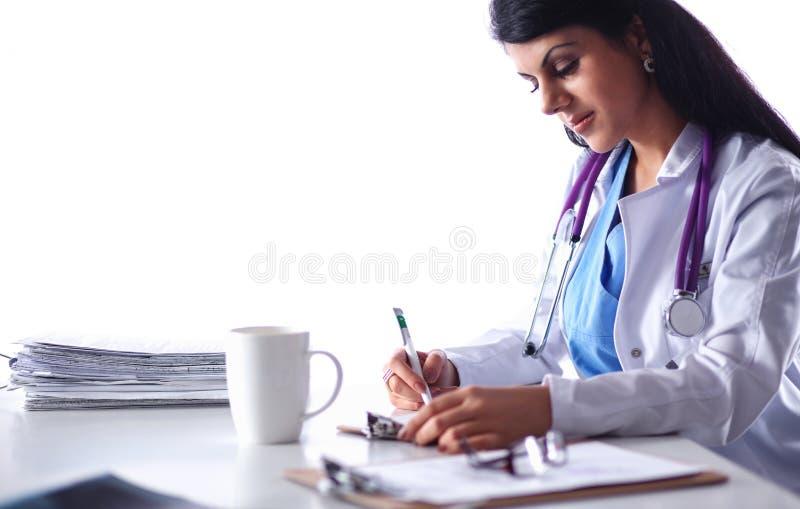 Medico femminile sorridente dei bei giovani che si siede allo scrittorio fotografie stock