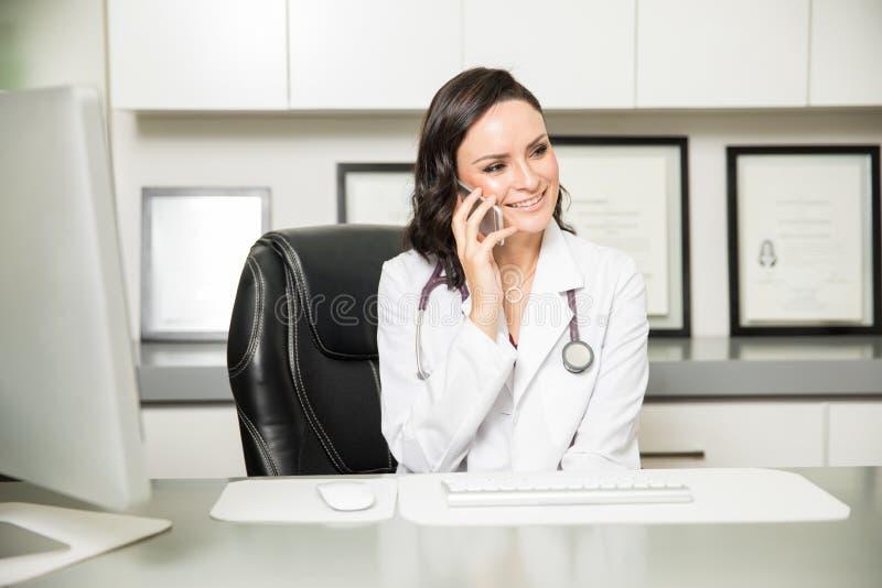 Medico femminile sveglio che discute a fondo il telefono fotografie stock libere da diritti