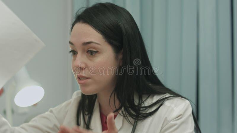 Medico femminile turbato fortemente parla, sorride e ride in isterico in gabinetto medico Estremi umani di emozioni immagini stock libere da diritti