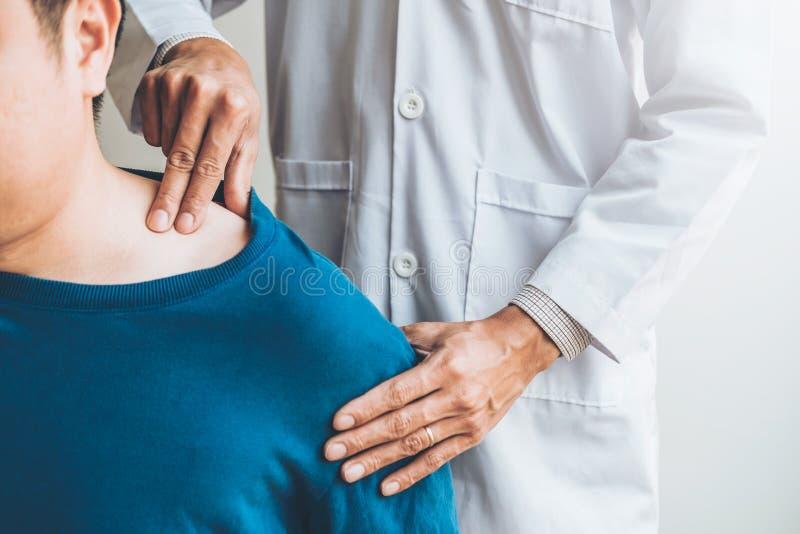 Medico fisico che consulta il paziente circa terapia fisica di problemi di dolore del muscule della spalla che diagnostica concet fotografia stock