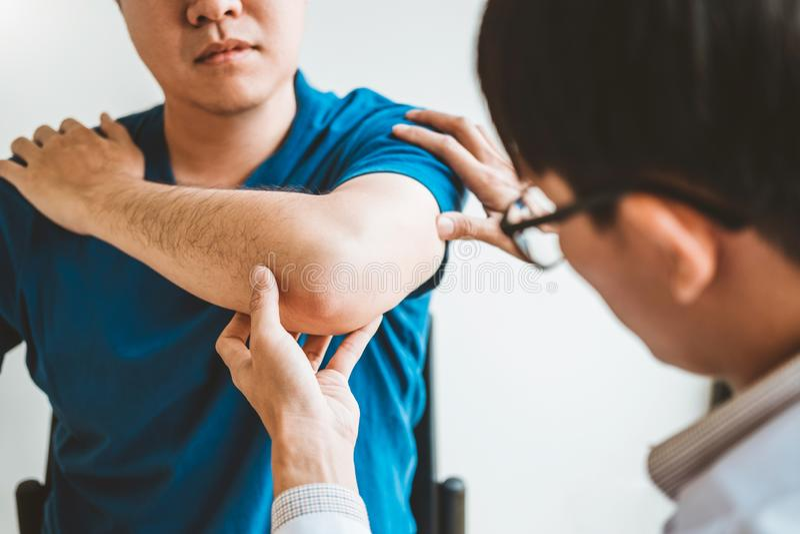 Medico fisico che consulta il paziente circa terapia fisica di problemi di dolore del muscule del gomito che diagnostica concetto fotografie stock