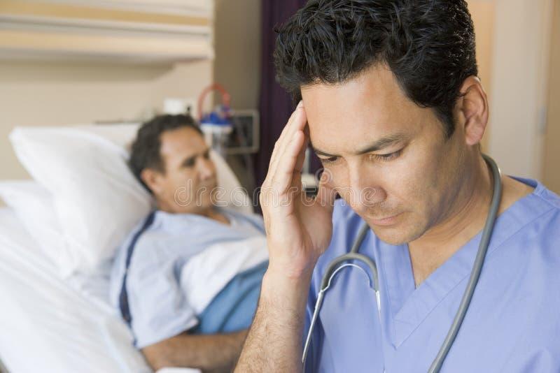 medico frustrato osservando la stanza dei pazienti immagini stock