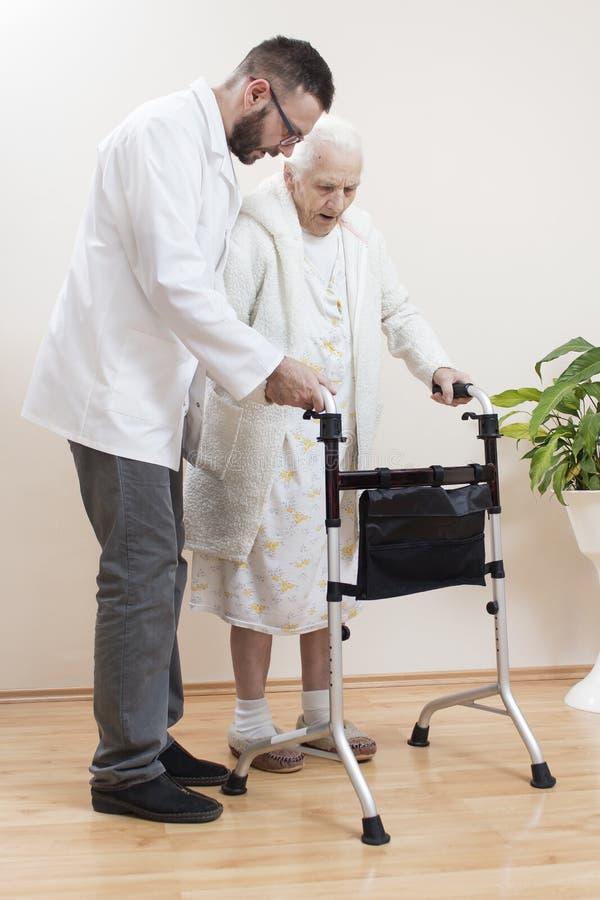 Medico geriatrico insegna a per camminare una donna anziana facendo uso di un camminatore di riabilitazione fotografie stock