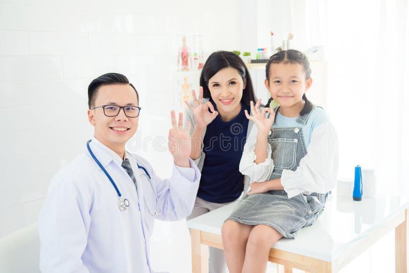 Medico, giovane ragazza paziente con la madre che fa approvazione di gesto immagini stock