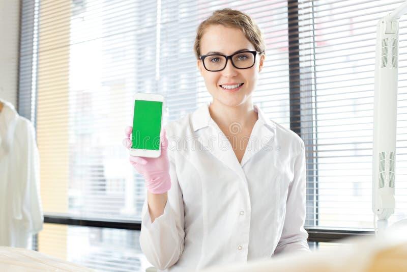 Medico grazioso con Smartphone moderno immagini stock